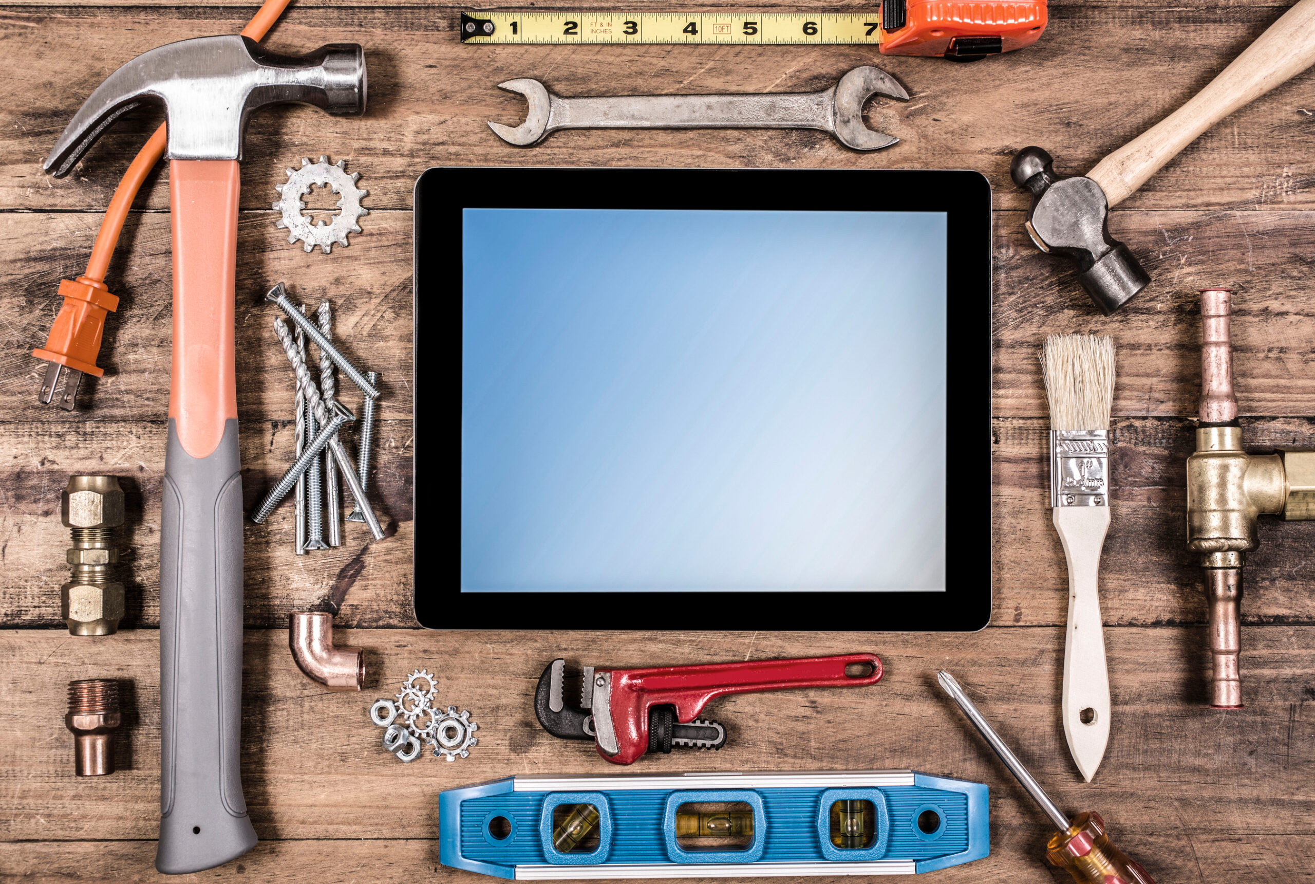 Various construction, DIY hand tools surround a digital tablet.  The screen is blue, blank on the tablet.  Tools include: hammer, nails, level, tape measure, paint brush, wrench, screwdriver.  All items lie on top of a rustic wooden table or desk.  Home improvement, construction themes.  Great background.